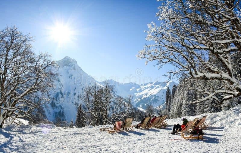 Grupo de personas que se sienta con las sillas de cubierta en montañas del invierno El tomar el sol en nieve Alemania, Baviera, A fotos de archivo libres de regalías