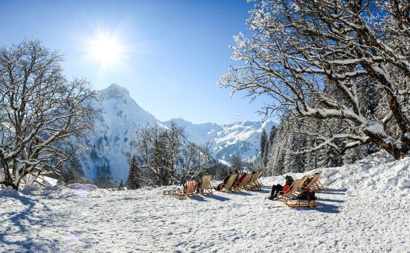 Grupo de personas que se sienta con las sillas de cubierta en montañas del invierno El tomar el sol en nieve Alemania, Baviera, A imagenes de archivo