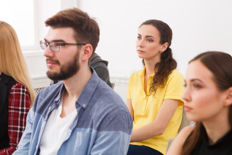 Grupo de personas que se sienta en el seminario, espacio de la copia imagenes de archivo