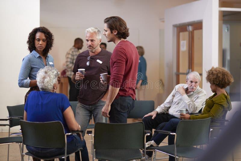 Grupo de personas que socializa después de la reunión en centro de la comunidad fotografía de archivo
