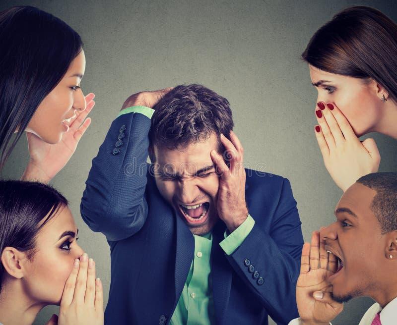 Grupo de personas que susurra a un hombre de negocios subrayado desesperado imagenes de archivo