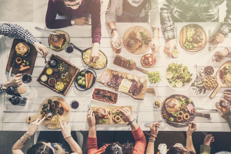 Grupo de personas que tiene cena de la unidad de la comida fotografía de archivo