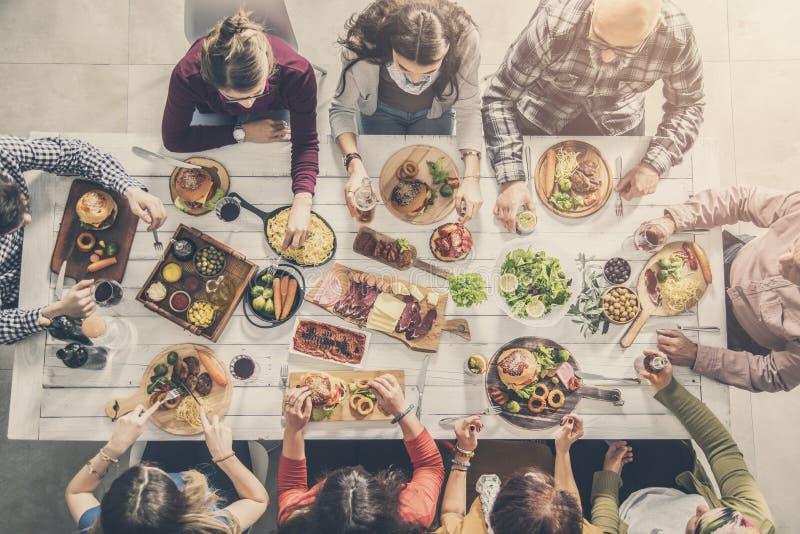 Grupo de personas que tiene comida junto foto de archivo