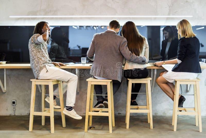 Grupo de personas que tiene una rotura en la cafetería fotos de archivo
