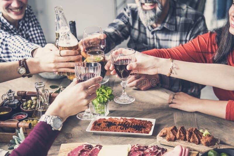Grupo de personas que tiene unidad de la comida que cena tostando los vidrios imagenes de archivo