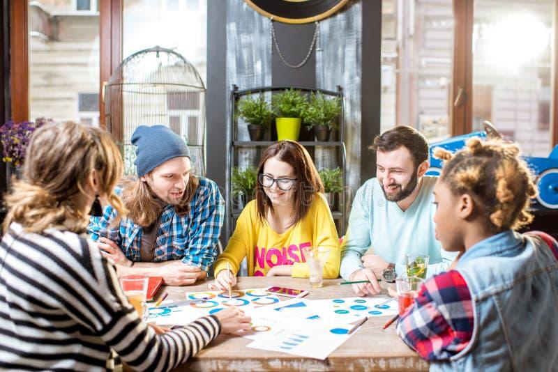 Grupo de personas que trabaja junto en el café fotos de archivo