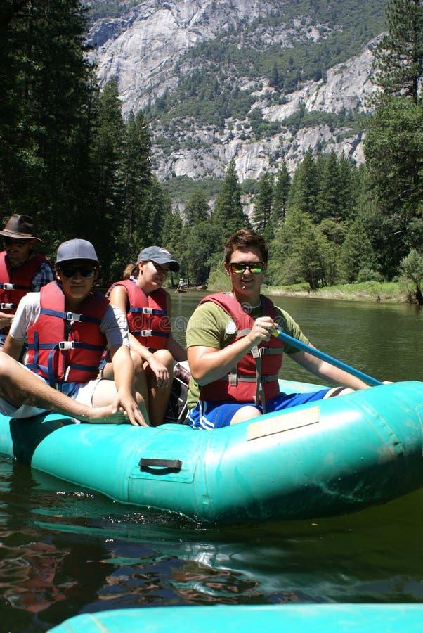 Grupo de personas que transporta en balsa rio abajo imagenes de archivo