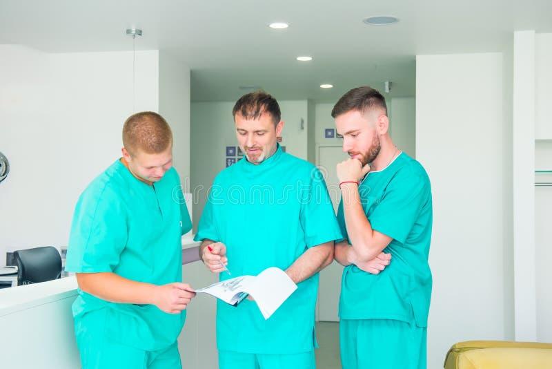 Grupo de pessoal médico que discute resultados pacientes na clínica Profissionais dos cuidados médicos que têm a discussão no hos fotos de stock