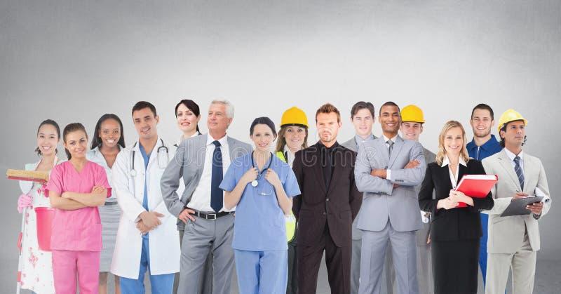 Grupo de pessoas com as profissões diferentes que estão na frente do fundo cinzento vazio foto de stock