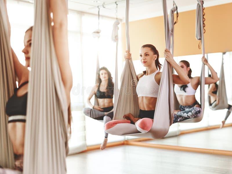 Grupo de pessoas contratado em uma classe de ioga Aero nas redes antigravitantes fotos de stock royalty free
