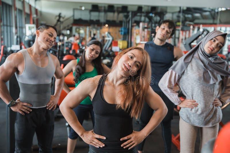 Grupo de pessoas dianteiro do olhar no fitness center que estica a w imagens de stock royalty free