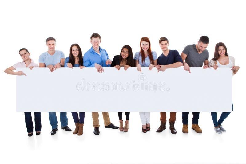 Grupo de pessoas diverso que apresenta a bandeira fotografia de stock royalty free