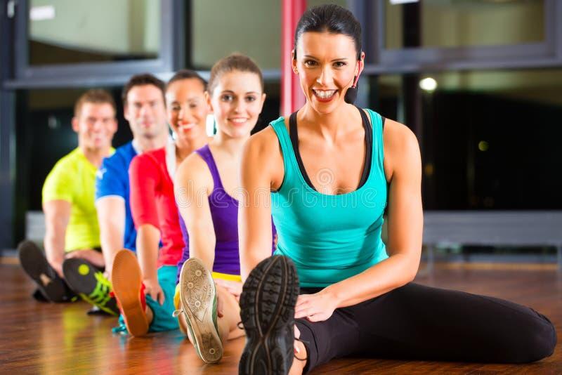 Grupo de pessoas e instrutor no esticão do gym fotografia de stock royalty free