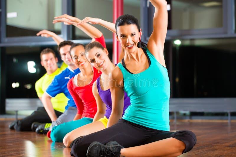 Grupo de pessoas e instrutor no esticão do gym imagem de stock