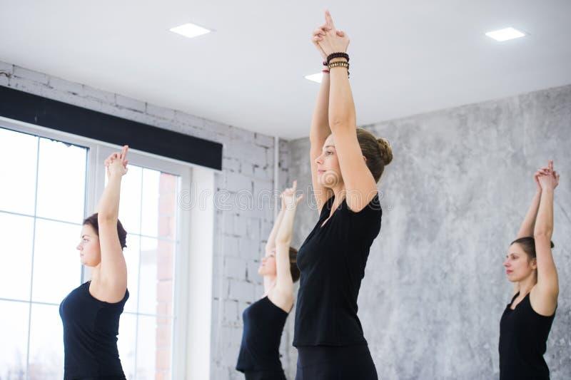 Grupo de pessoas de ensino do instrutor fêmea caucasiano da ioga, aptidão, esporte e conceito saudável do estilo de vida Jovens m imagens de stock royalty free