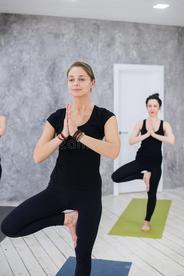 Grupo de pessoas de ensino do instrutor fêmea caucasiano da ioga, aptidão, esporte e conceito saudável do estilo de vida Jovens m fotografia de stock royalty free