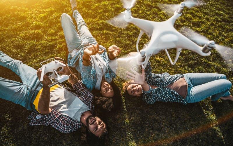 grupo de pessoas Multi-étnico na grama e no zangão do voo fotografia de stock royalty free