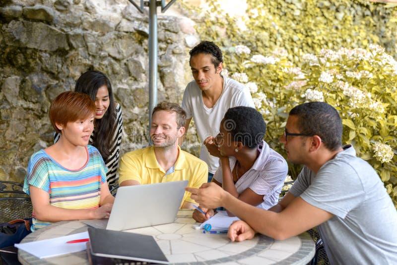 Grupo de pessoas multicultural que discute pelo portátil imagem de stock royalty free