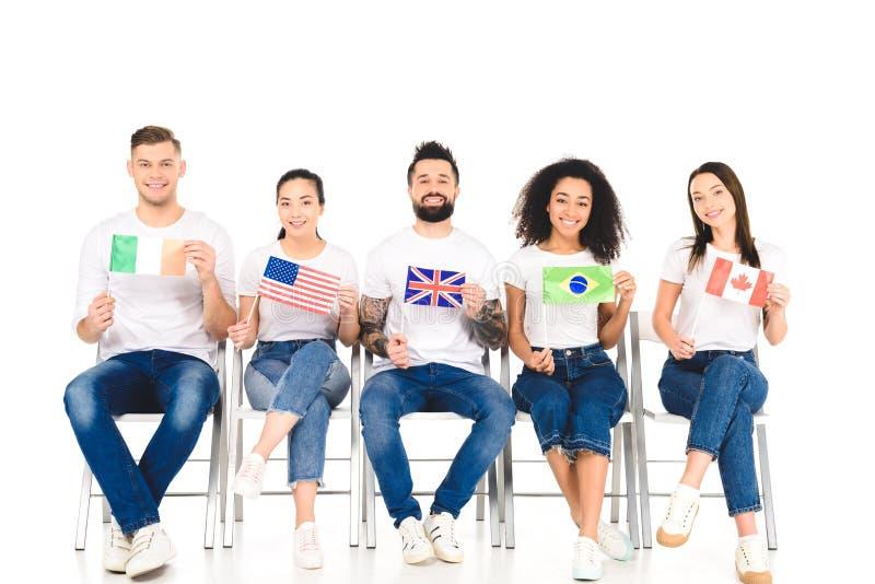 grupo de pessoas multicultural que senta-se em cadeiras com as bandeiras dos países diferentes isolados fotografia de stock