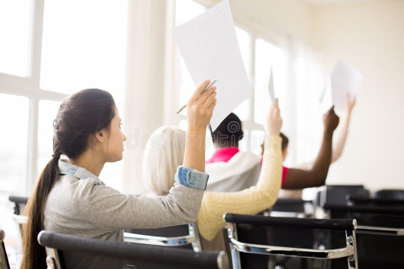Grupo de pessoas multirracial que levanta as mãos com papéis no treinamento fotos de stock