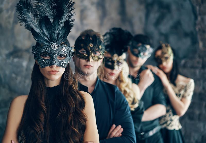 Grupo de pessoas na máscara do carnaval do disfarce que levanta no estúdio imagem de stock royalty free