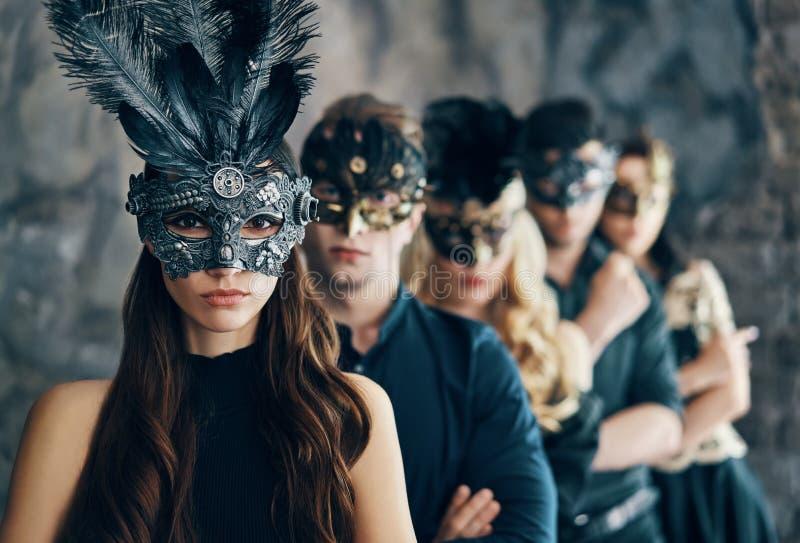 Grupo de pessoas na máscara do carnaval do disfarce que levanta no estúdio foto de stock royalty free