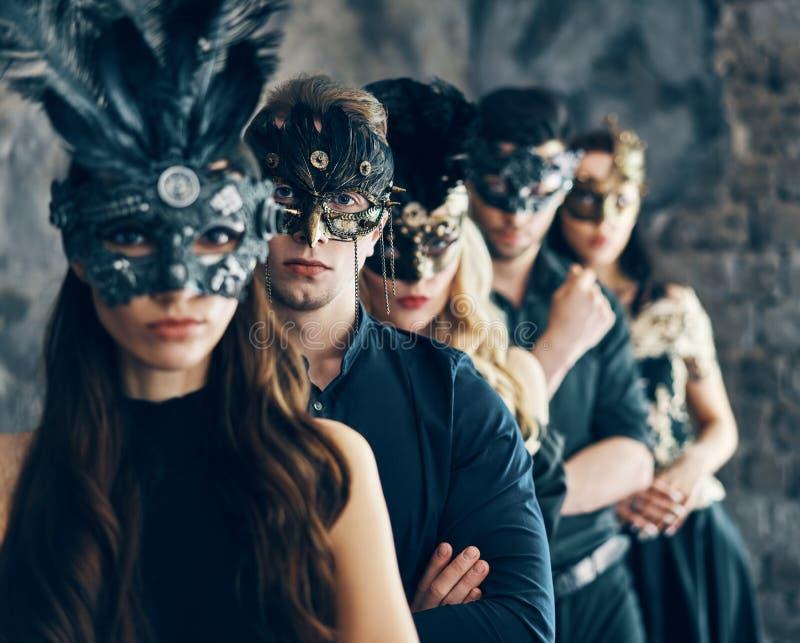 Grupo de pessoas na máscara do carnaval do disfarce que levanta no estúdio imagem de stock