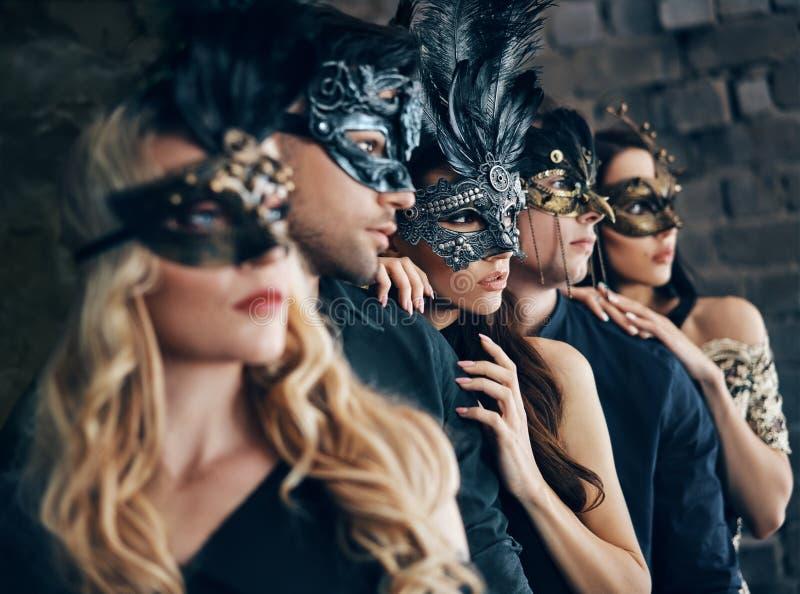 Grupo de pessoas na máscara do carnaval do disfarce que levanta no estúdio fotos de stock royalty free