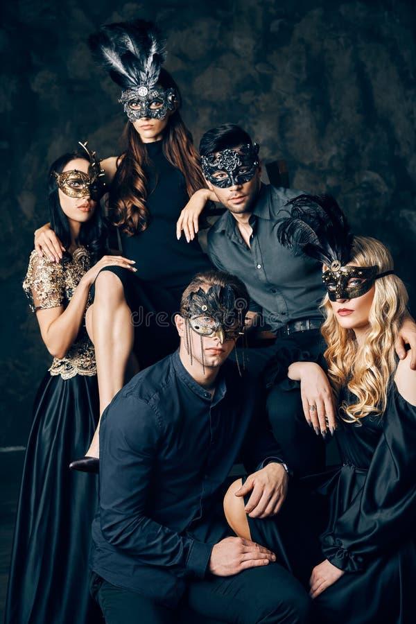 Grupo de pessoas na máscara do carnaval do disfarce que levanta no estúdio fotografia de stock