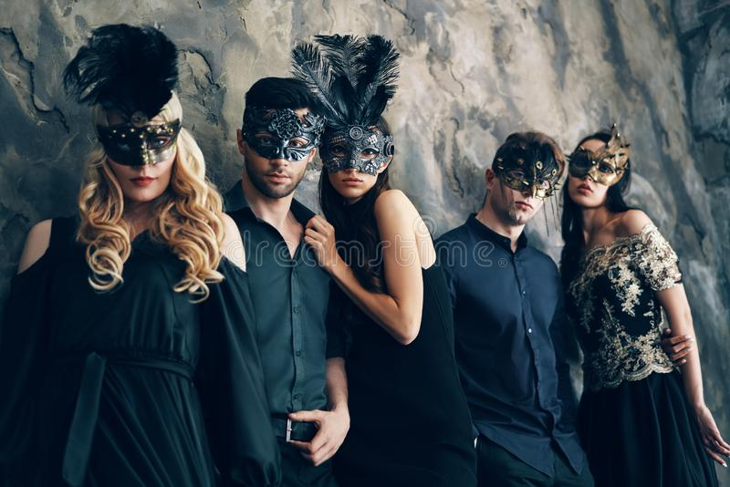 Grupo de pessoas na máscara do carnaval do disfarce que levanta no estúdio fotografia de stock royalty free