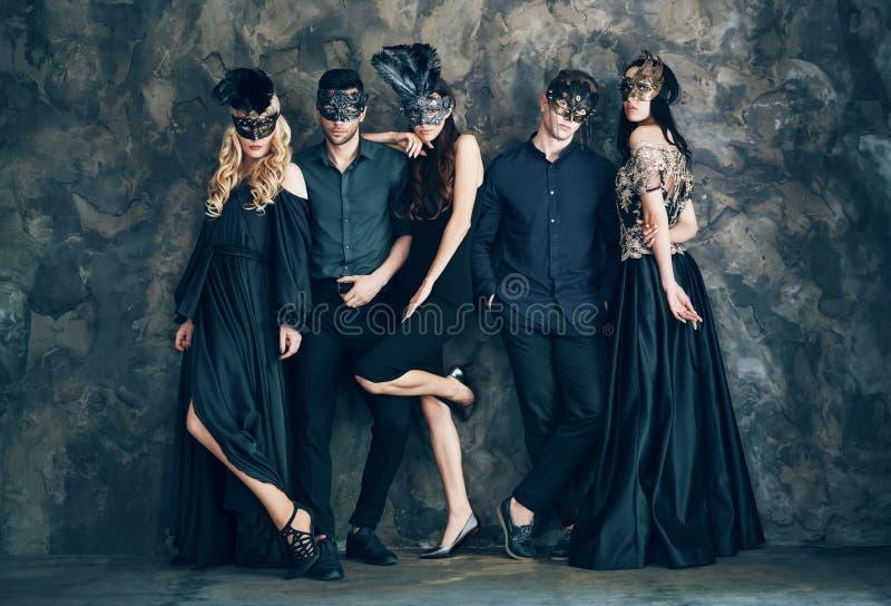 Grupo de pessoas na máscara do carnaval do disfarce que levanta no estúdio imagens de stock royalty free