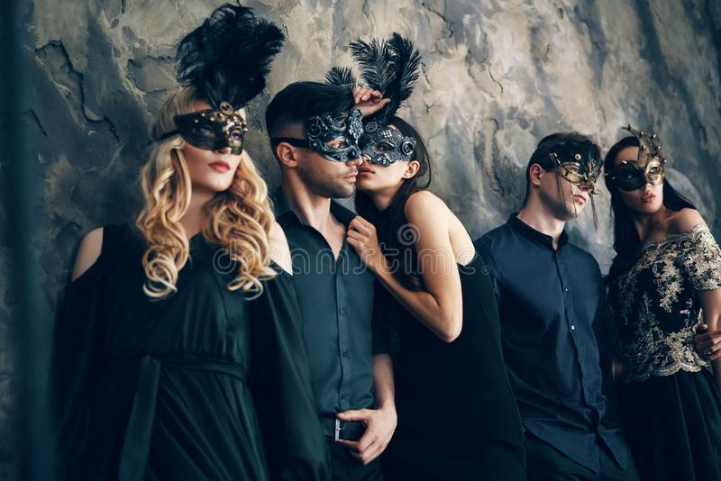 Grupo de pessoas na máscara do carnaval do disfarce que levanta no estúdio foto de stock
