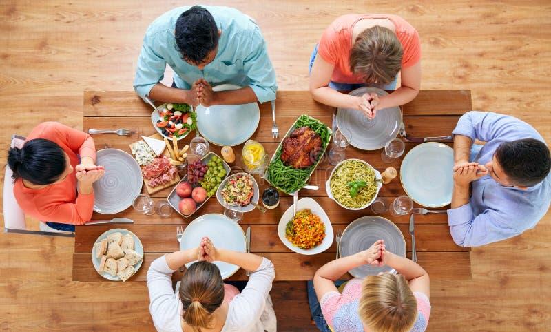 Grupo de pessoas na tabela que reza antes da refeição imagem de stock