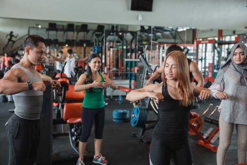 Grupo de pessoas no gym que estica para aquecer-se imagem de stock
