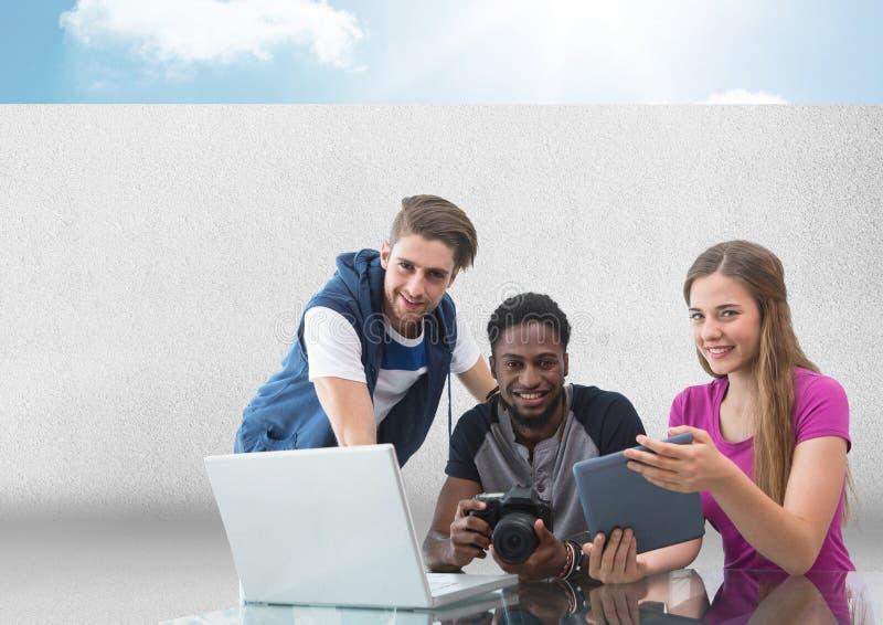 Grupo de pessoas no portátil com a câmera na frente do fundo cinzento com céu fotos de stock royalty free