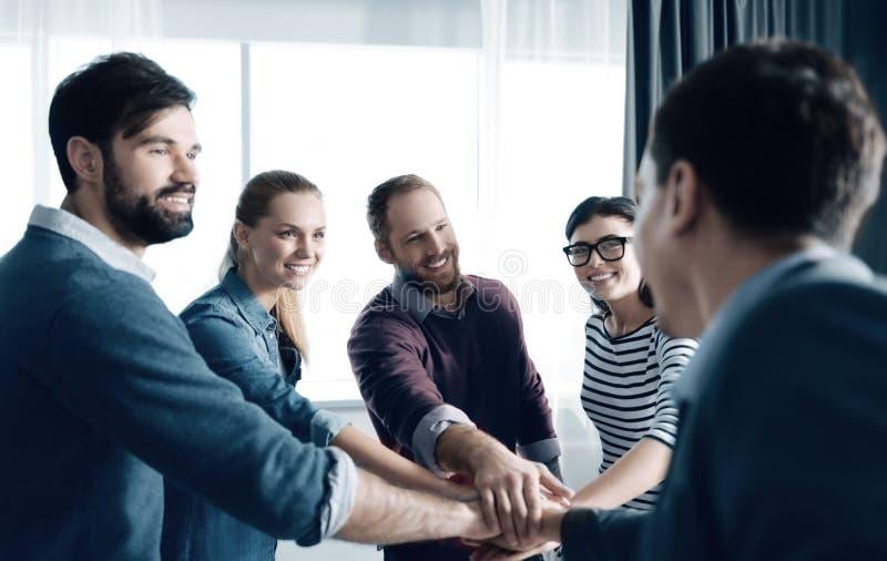 Grupo de pessoas novo alegre que mantém as mãos unidas foto de stock royalty free