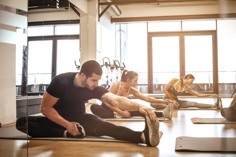 Grupo de pessoas pequeno que estica no gym imagens de stock royalty free