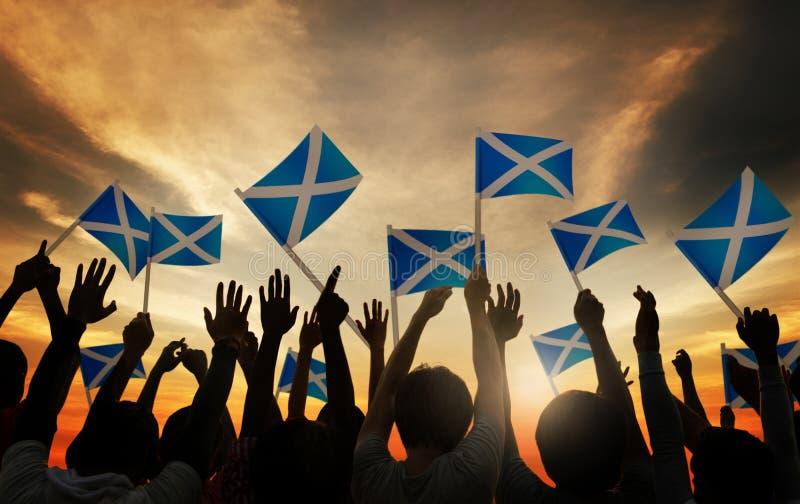 Grupo de pessoas que acena bandeiras escocesas no Lit traseiro imagem de stock royalty free
