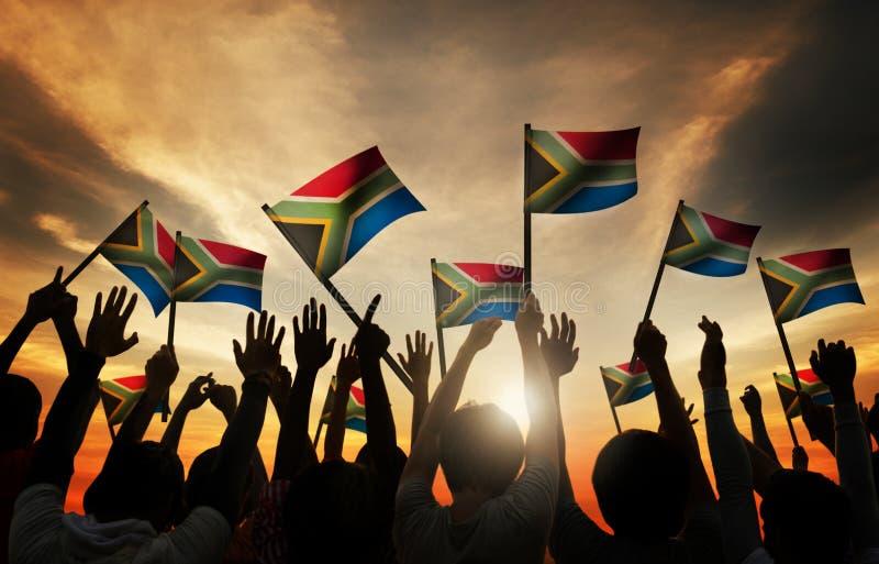 Grupo de pessoas que acena para o sul - bandeiras africanas no Lit traseiro imagem de stock royalty free