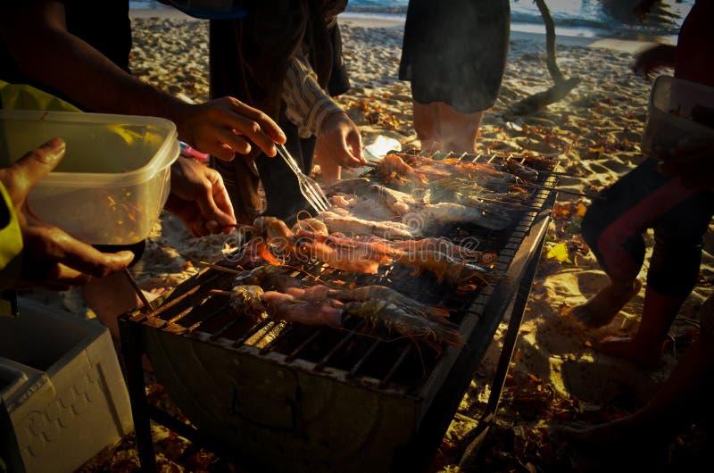 Grupo de pessoas que ajuda-se a fazer o jantar delicioso antes do por do sol na praia em Tailândia imagens de stock