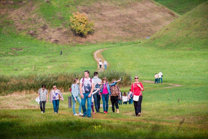 Grupo de pessoas que anda perto dos montes de Kernave imagens de stock royalty free