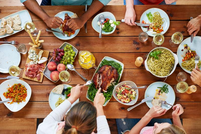 Grupo de pessoas que come a galinha para o jantar fotos de stock