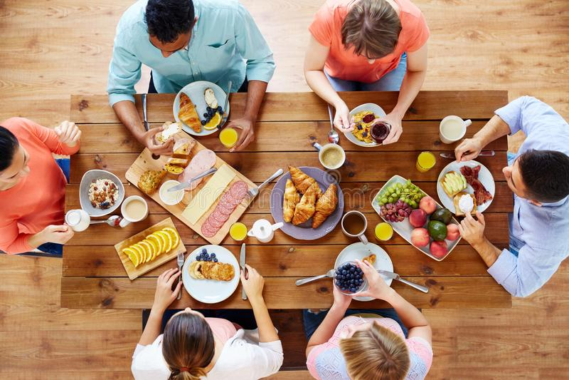 Grupo de pessoas que come o café da manhã na tabela foto de stock