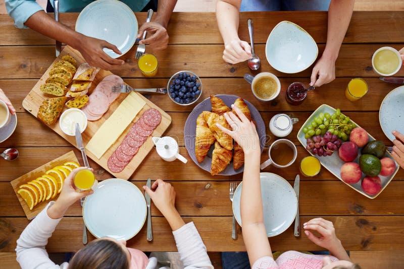 Grupo de pessoas que come o café da manhã na tabela imagens de stock royalty free