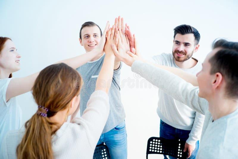 Grupo de pessoas que dá a elevação cinco fotografia de stock royalty free
