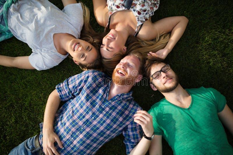 Grupo de pessoas que encontra-se na grama foto de stock