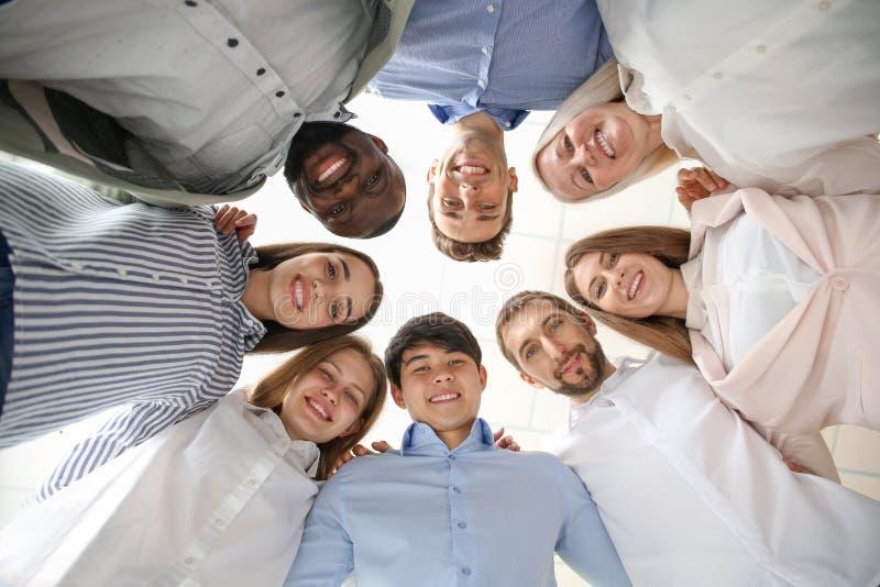 Grupo de pessoas que está junto contra o fundo claro, vista inferior Conceito da unidade foto de stock royalty free