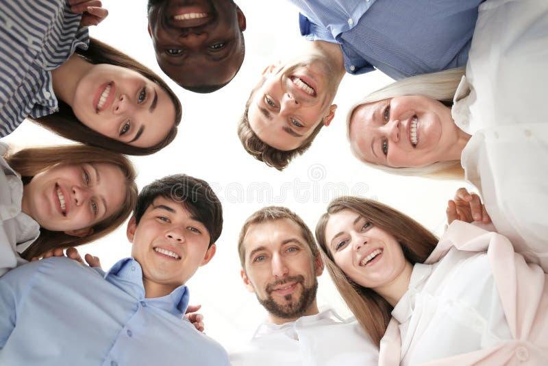 Grupo de pessoas que está junto contra o fundo claro, vista inferior Conceito da unidade fotografia de stock