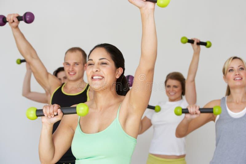 Grupo de pessoas que exercita no estúdio da dança com pesos imagem de stock