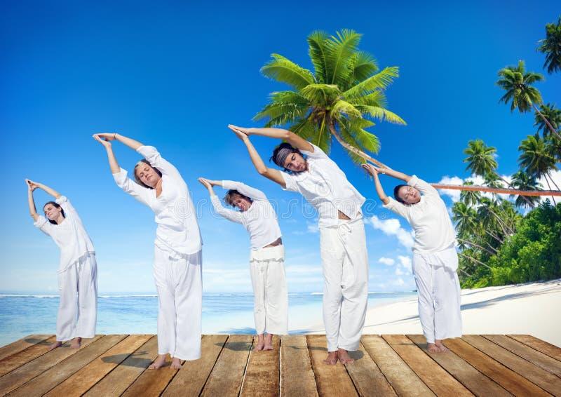 Grupo de pessoas que faz a ioga na praia foto de stock
